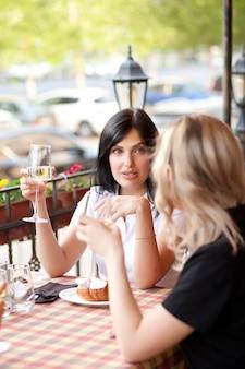 Женщины в кафе пьют белое вино и разговаривают. концепция общения и дружбы.