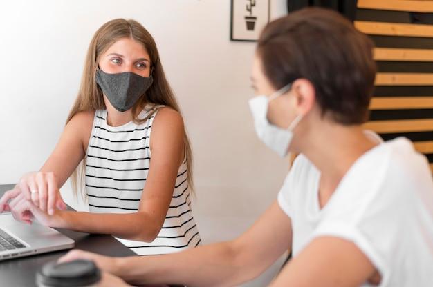 マスクを身に着けているラップトップでテラスで女性