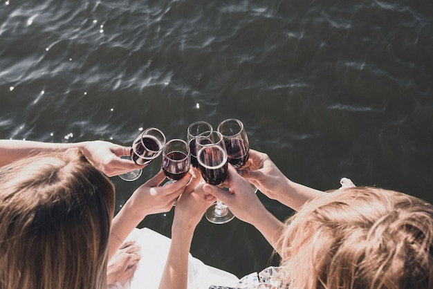 Women at a bachelorette party near river drinking red wine
