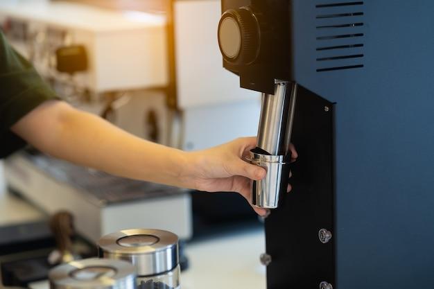 コーヒーマシンでコーヒーを作る女性バリスタ、コーヒーメーカーのコンセプト