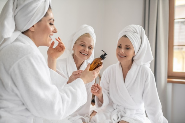 Women in bathrobes trying new cosmetic
