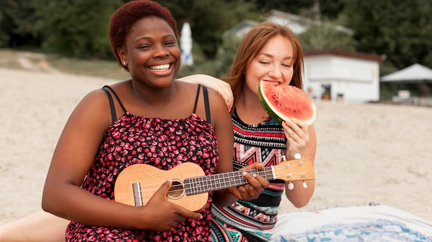 Women at the beach enjoying watermelon and playing guitar