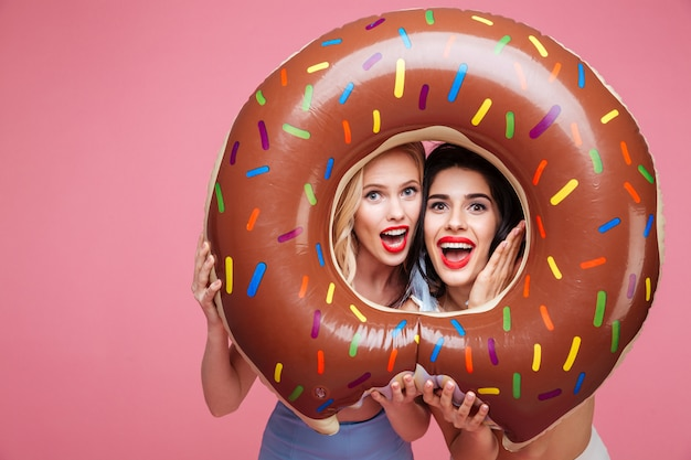 Women in beachwear having fun with donut shaped heart mattress