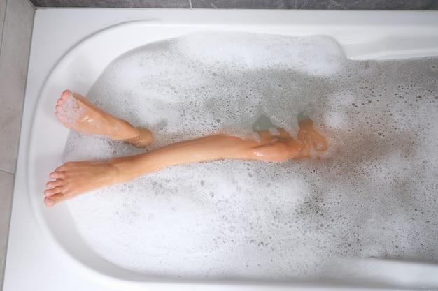 Красивые стройные ноги женщины в ванне с водой и пеной