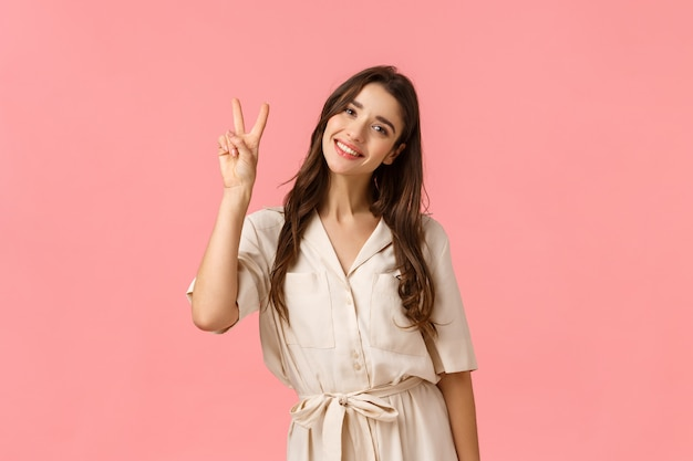 Women, beauty and advertising concept. cheerful tender brunette woman feeling relaxed and delighted, smiling lovely, tilt head coquettish as wearing dress showing peace sign, pink wall