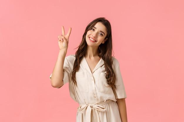 女性、美容、広告のコンセプトです。ピースサイン、ピンクの壁を示すドレスを着ているとリラックスして喜んで、素敵な笑顔、チルトヘッドコケティッシュな陽気な優しいブルネットの女性