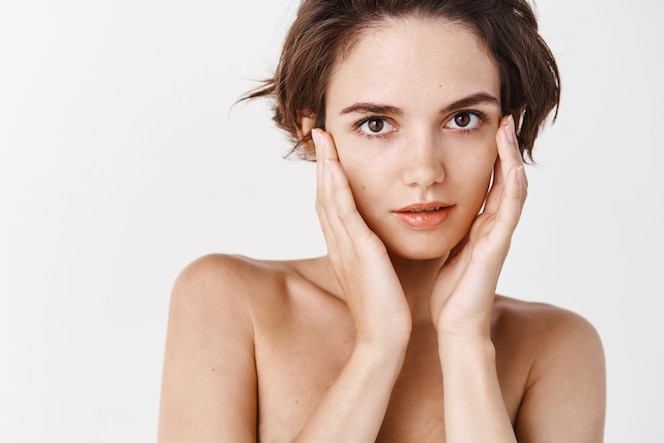 Women beauty. tender girl standing half naked and touching healthy no makeup skin, showing hydrated and smooth face after facial cleansing gel, white wall