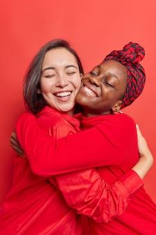 여성의 가장 친한 친구는 긴 이별 후 매우 그리운 서로를 만나서 반가워 부드러운 순간을 즐기며 캐주얼한 빨간 옷을 입고 따뜻한 관계를 갖습니다