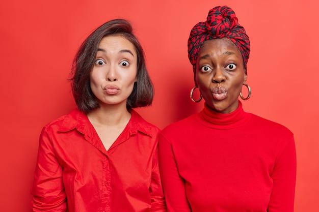 Le migliori amiche delle donne stanno vicine l'una all'altra mantengono le labbra arrotondate aspettano il bacio indossano abiti rossi posano sulla parete luminosa dello studio. modelli femminili di razza mista con labbra increspate. espressioni del viso