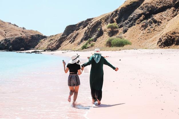 Women best friends in summer hat enjoying vacation in pink sand beach