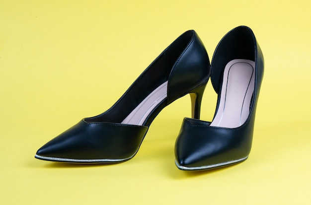 Women black classic shoes on a yellow floor