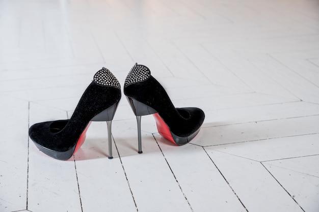 かかとに光沢のあるラインストーンが付いた装飾的な弓の要素を持つ女性の黒いスエードのハイヒールの靴