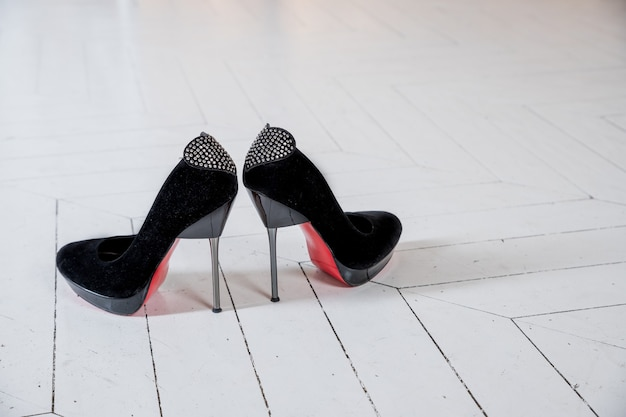 Women black suede high heel shoes with a decorative bow element with shiny rhinestones on heel