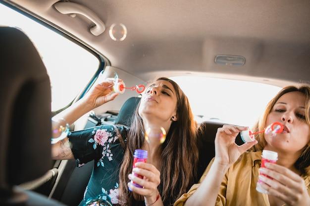 Women blowing bubbles in car