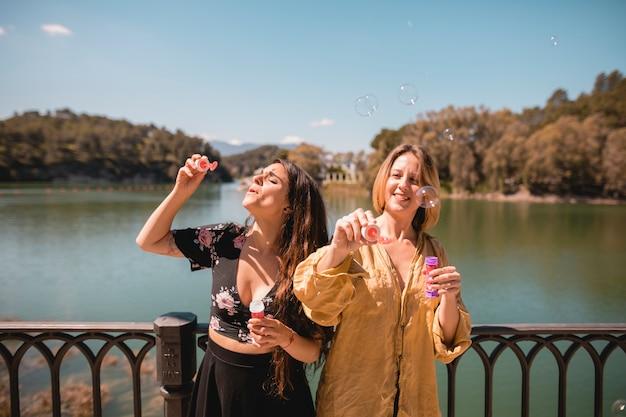 Women blowing bubbles near river