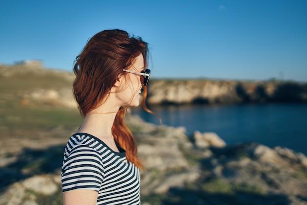 川の近くで女性が吹く振り返りと青空の風景の側面図