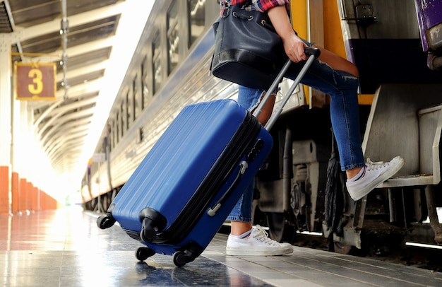 Women and the blue suitcase are going up the train ladder.