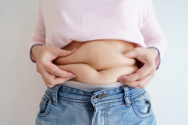Women body fat belly. obese woman hand holding excessive belly fat. diet lifestyle concept to reduce belly and shape up healthy stomach muscle.