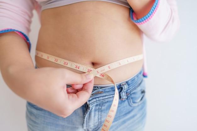 여성 체지방 배. 과도한 배꼽 지방을 들고 뚱뚱한 여자 손. 다이어트 라이프 스타일 개념은 배를 줄이고 건강한 복근을 형성합니다.