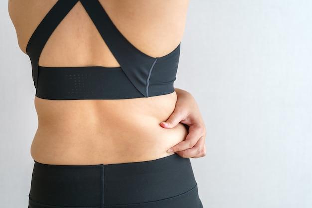 여성 체지방 배. 과도한 배꼽 지방을 들고 뚱뚱한 여자 손. 다이어트 라이프 스타일 개념