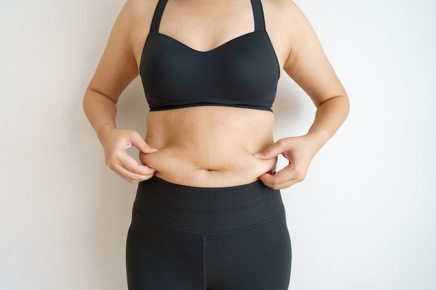Women body fat belly. obese woman hand holding excessive belly fat.
