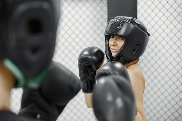 Boxe femminile. principianti in palestra. signora in abbigliamento sportivo nero.
