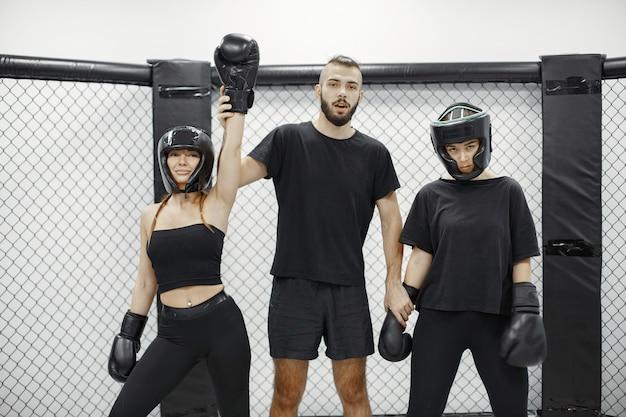 Boxe femminile. il giudice annuncia il vincitore. signora in abbigliamento sportivo nero. donne con allenatore.