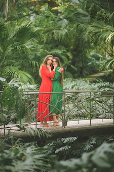 Women on a bridge surrounded by foliage