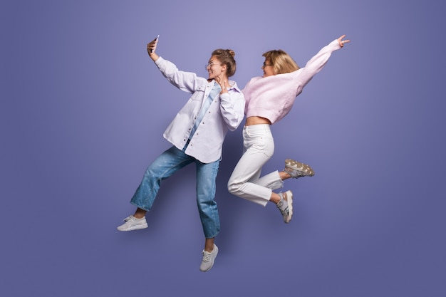 Women in bright clothes and blonde hair jumping on a violet studio wall