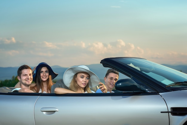Women in brim broad hats and men sitting in silver cabriolet.