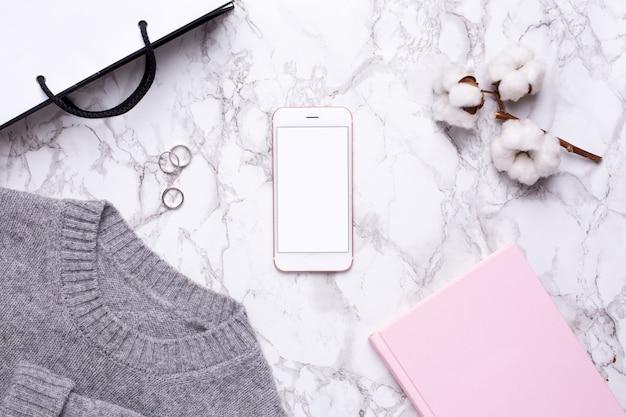 Женский рабочий день с мобильным телефоном и розовым блокнотом на мраморном столе