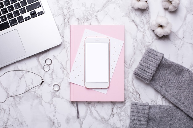 Women business day with mobile phone,keyboard and pink notebook on marble table