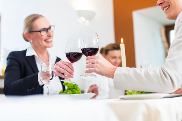 Women on business lunch toasting with wine