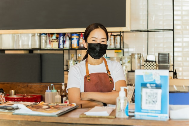 カウンターで防護マスクスタンドを着ている女性カフェのオーナー