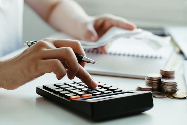 여성은 집에서 국내 지폐를 계산합니다. 현대 사무실에서 계산기를 사용하고 균형과 비용을 확인하십시오.