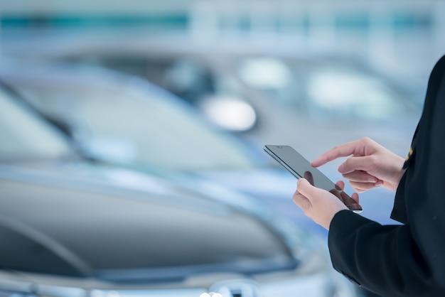 女性の自動車販売員は自動車ショールームでモバイルスマートフォンを使用