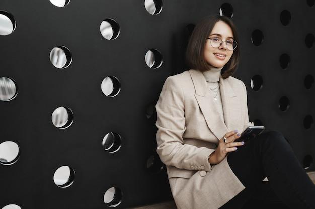 Concetto di carriera, istruzione e persone delle donne. il ritratto della donna attraente intelligente che si siede sul pavimento e sulla parete magra come rilassante, ha una pausa dopo i corsi, tenendo il telefono cellulare e sorridendo felice.