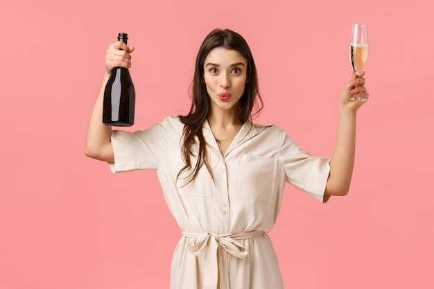 Women, celebration and party concept. fashionable good-looking brunette female in dress, having fun, praying, open champagne bottle, raising glass suggesting drink and celebrate