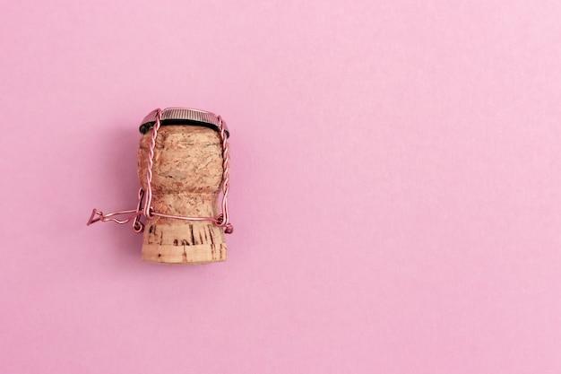 Женский персонаж из пробки шампанского вина и металлического мюзле на розовом