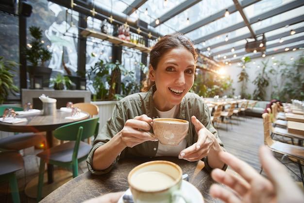 コーヒーを飲みながら積極的におしゃべりする女性