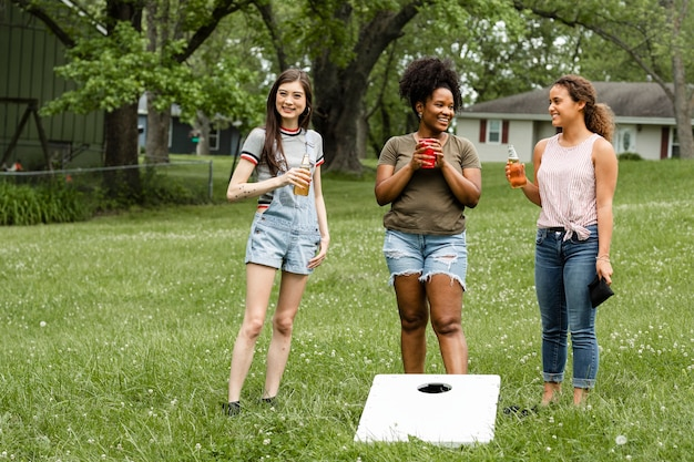 Women chatting during a cornhole game in the park