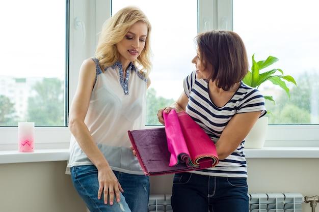 女性は新しい家でカーテンの生地やアクセサリーを選びます。
