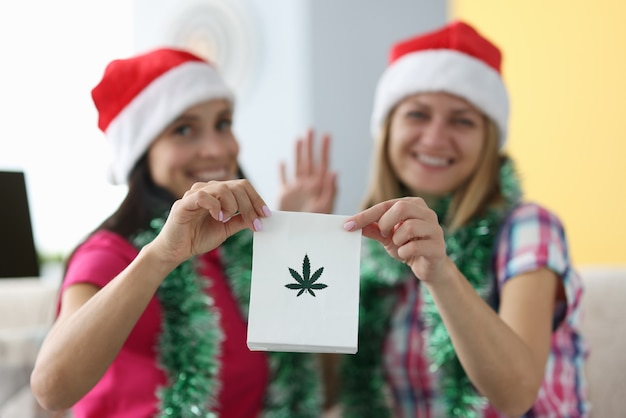 Women in christmas hats are holding bag of marijuana leaves and waving