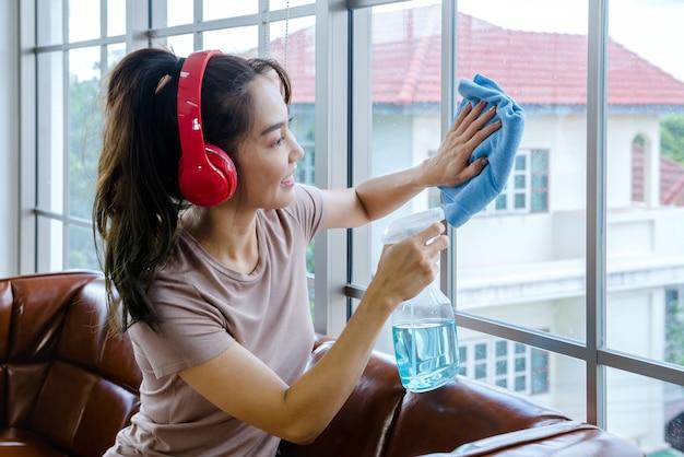 女性は家を衣服と液体で掃除します。
