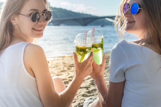 女性はモヒートのグラスをチャリンという音し、振り返って、海に座ってさわやかなカクテルを飲みます