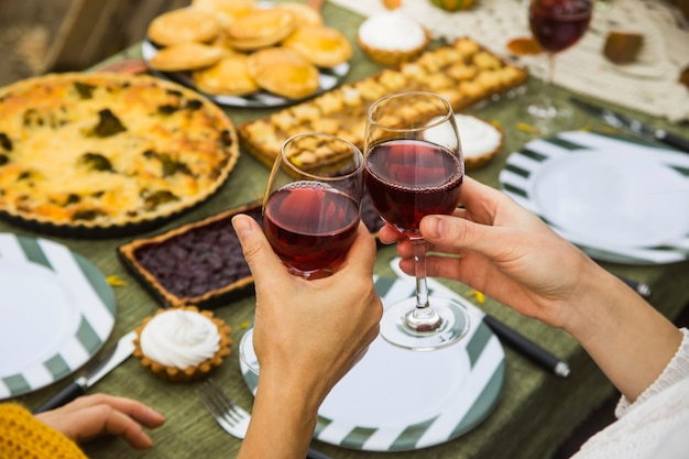 Women clink glasses of wine at a brunch table of pastries.