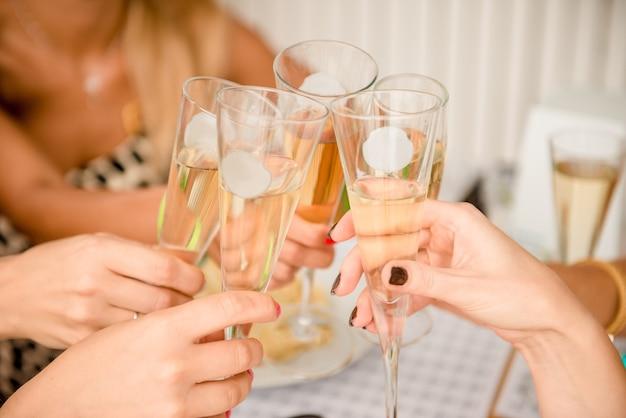 シャンパングラスをチリンと鳴らす女性