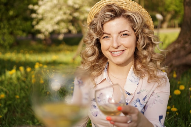 Women clinking glasses with tasty wine on light background at summer day. happy blonde with curly hair in a straw hat