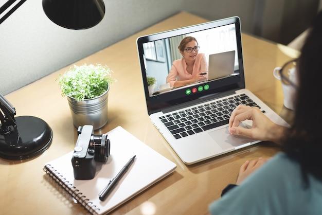 自宅で仕事をしながらラップトップコンピューターでビデオ通話を行う女性の同僚。ビジネスウーマンパートナーチームは、職場での会議でインターネットを介してビジネスを話しています。