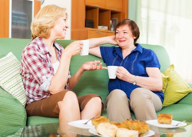昼食のために休憩中にお茶を飲んで話す女性の同僚